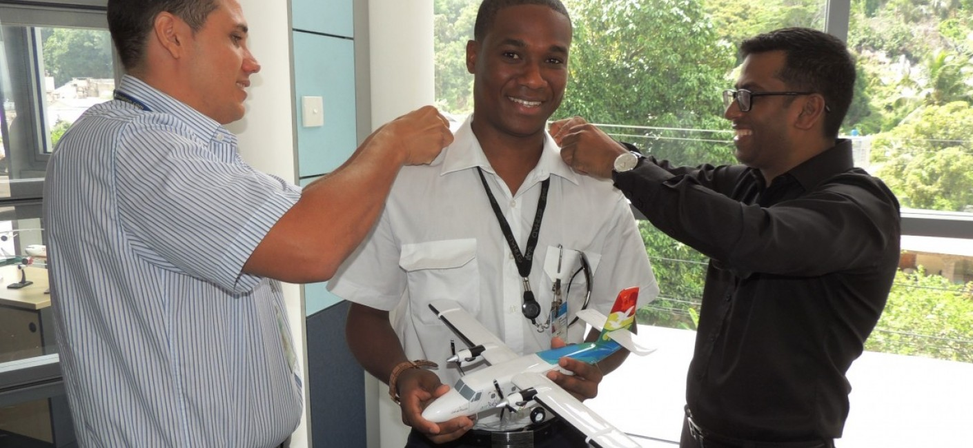 Captain Sandy Benoiton, Head of Crew Training (left) and Manoj Papa, Air Seychelles' Chief Executive Officer (right), fasten Captain Morel's epaulettes as he holds a model of the Twin Otter aircraft he now commands